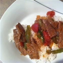 Steak and Rice Recipe - Round steak strips are sauteed with green pepper and simmered with diced tomatoes, garlic, and ginger in this easy meal. Serve over steamed rice.