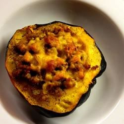 Stuffed Acorn Squash II Recipe - Acorn squash stuffed with ground beef, pork sausage, onions, garlic, and cheddar cheese. Serve with tossed salad and crusty bread for a simple, tasty meal.