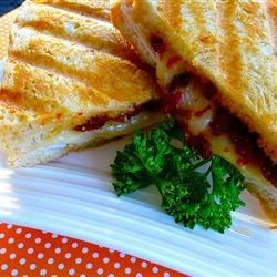 Turkey and Sun-dried Tomato Panini Recipe - Turkey, provolone cheese, and sun-dried tomatoes are sandwiched between two slices of bread in a panini maker for a savory, flavorful lunch.