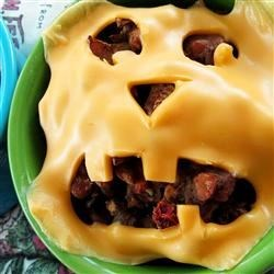 Halloween Jack-o'-Lantern Beef Pies Recipe - Kids will love these baked biscuit cups filled with seasoned ground beef and topped with fun Halloween pumpkin faces made of cheese.