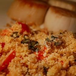 Company Couscous Recipe - Savory couscous flavored with garlic, red bell pepper, scallions, tomatoes and basil, and topped with parmesan cheese.