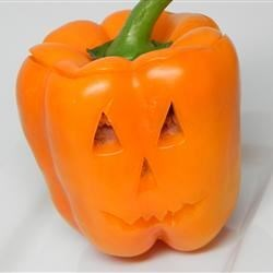 Mexican Stuffed Peppers Recipe - Bell peppers stuffed with layers of Mexican-inspired ingredients are perfect for Halloween dinner, especially if you carve scary faces into the peppers before baking.