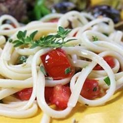 Pasta Basico Recipe - Garlic, thyme and fresh tomatoes and olive oil are tossed with spaghetti. Topped with grated cheese, this dish is simple and savory.
