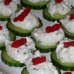 Cucumber Crab Snacks Recipe - Cucumber slices are adorned with cream cheese, crabmeat, and a dollop of cocktail sauce.