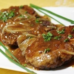Hamburger Steak with Onions and Gravy Recipe - An easy-to-make classic featuring tasty hamburger 'steaks' smothered in gravy and onions. It's a great way to dress up a pound of ground beef, and you probably have all the ingredients on hand!