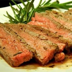 Tuscan Flank Steak Recipe - Flavorful flank steak is marinated for several hours in a marinade of lemon zest, olive oil, rosemary, and garlic, then grilled to perfection.