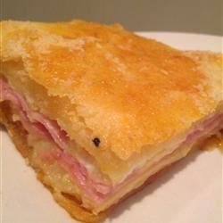 Spicy Ham and Cheese Squares Recipe - These spicy ham and cheese squares are a great appetizer for your next party. Ham, pepperoni, salami, Swiss cheese, and provolone cheese are sandwiched between crescent roll dough and baked to perfection.