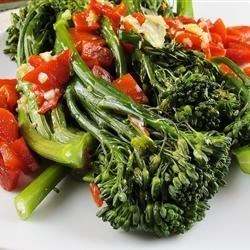 Broccoli Rabe with Roasted Peppers Recipe - Deliciously peppery broccoli rabe (rapini) is cooked with extra virgin olive oil and garlic, then sprinkled with Parmesan cheese to serve in this authentic Italian dish.