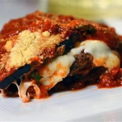 Eggplant Parmesan with Fresh Basil and Smoked Mozzarella Recipe - A gourmet version of the Italian-inspired favorite dish has plenty of fresh basil, smoked mozzarella cheese, and rich marinara sauce covering delicious fried eggplant slices.
