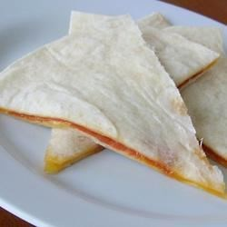 2 Minute Cheese Quesadillas Recipe - Cheddar cheese and flour tortillas are all you need for these quick and easy quesadillas. Cook in the microwave for 1 minute and lunch is served!