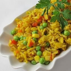 Awesome Rice Pilaf Recipe - A colorful and savory herbed rice dish with carrots, red bell peppers, corn, and peas makes a great side to serve alongside chicken or pork.