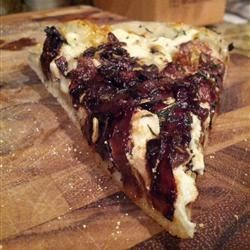 Sundried Tomato and Onion Pizza Recipe - Pan-fried onions and sun-dried tomatoes are sprinkled with goat cheese and provolone cheese onto a thin pizza crust for quick and easy Italian-inspired dinner.