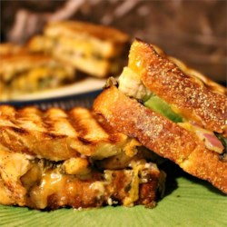 Chicken Pesto Paninis Recipe and Video - A delicious mix of chicken, pesto, veggies, and cheese all melted together on flavorful focaccia bread. Simple, fast, and very tasty - a nice change from normal sandwiches.