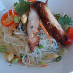 Spicy Rice Noodle Salad Recipe - Grilled chicken thighs top this main dish salad that showcases the spicy and sweet flavors of Thai food. Toss with fresh herbs, vegetables, and crunchy peanuts for a simple and light-tasting meal.