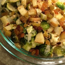 Roasted Brussels Sprouts with Apples, Golden Raisins, and Walnuts Recipe - Brussels sprouts are roasted with apples and cauliflower and tossed with golden raisins and walnuts for a sweet and savory side dish.