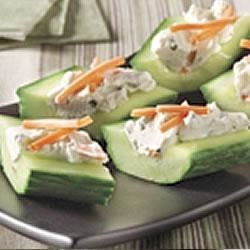 Cream Cheese 'n Herb Cucumber Bites Recipe - So fast and easy, hollowed out cucumber 'boats' are filled with a creamy chive and onion mixture with grated carrots, then cut into bite-size pieces.
