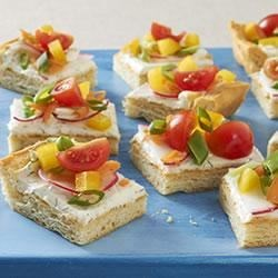 Spring Veggie Pizza Appetizer Recipe - A medley of colorful spring veggies like sugar snap peas, cherry tomatoes, and radishes top a creamy 'sauce' on a golden dinner-roll crust for these tasty appetizer bites.