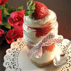 Strawberry Cheesecake in a Jar Recipe - Quick and easy individual cheesecakes are layered in jars and topped with sliced strawberries for a fun, kid-pleasing way to enjoy dessert.