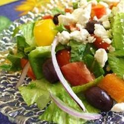 Greek Salad I Recipe - An oregano/olive oil dressing with a dash of lemon makes this traditional salad just a bit different. All the veggies, including the Romaine, are chopped so when the salad is tossed, each bit of tomato or pepper, or cucumber gets its equal share of dressing. Six servings.