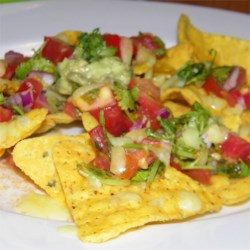 Classic Pub Style Nachos Recipe - Nachos baked with bubbling Cheddar cheese and fresh tomato salsa make a bright and colorful snack for a party or watching the game.