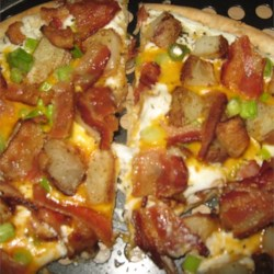 Baked Potato Pizza Recipe - Perfect for Super Bowl parties or any other gathering, this pizza is loaded with bacon, green onions, cheese, and sour cream. It tastes just like a baked potato!