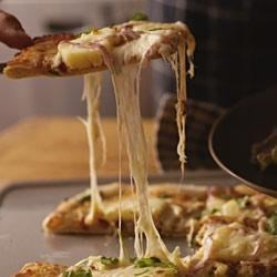 Big Island Pizza Recipe - For a taste of paradise on pizza night, top homemade pizza crust with barbecue sauce, pulled pork, pineapple chunks, and shredded mozzarella.