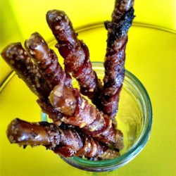 Bacon Wrapped Pretzels Recipe - Pretzel rods are wrapped in spicy brown sugar-coated bacon slices and baked for a sweet and savory appetizer perfect for your next get-together.