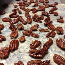 Frosted Pecan Bites Recipe - Toasted pecans are candied in the oven in a butter, sugar and egg white glaze.  Serve as an appetizer, or in bowls on the dinner table during dessert.
