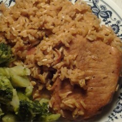 Pork Chops Over Rice Recipe - Browned pork chops simmer with spicy bacon- and chicken broth-flavored rice in this easy one-pot meal.