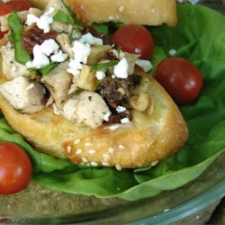 Chicken and Sun-Dried Tomato Bruschetta Recipe - Marinated chicken, spinach, feta, and sun-dried tomatoes are tossed with dressing and served on grilled or toasted slices of focaccia bread. This is a great appetizer any time of year!