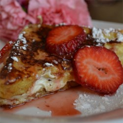 Strawberry Cheesecake French Toast  Recipe - Cream cheese-stuffed French toast is served with a sweet and warm strawberry glaze and topped with whipped cream in this decadent breakfast favorite.