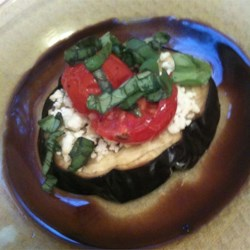 Eggplant with Feta Cheese Recipe - This simple side dish is essentially slices of eggplant topped with feta cheese and fresh basil.