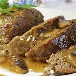 Divine Meatloaf Recipe - A fresh twist on a classic dish. This meatloaf incorporates green pepper, green onions, and sliced mushrooms into the ground beef, and is topped with ketchup and brown sugar.