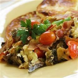 Aussie Breakfast Egg Mess Recipe - Give scrambled eggs some savory add-ins with this tasty combination from Down Under. Sauteed onions and bell pepper, mushrooms, and bacon are stirred into beaten eggs along with grated cheese and diced tomatoes.
