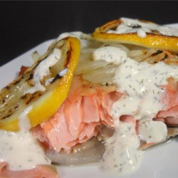 Salmon with Creamy Dill Sauce Recipe - A dill sauce with sour cream, mayonnaise, and horseradish accompanies a salmon fillet baked in a sealed aluminum foil packet for a centerpiece entree for the dinner table.