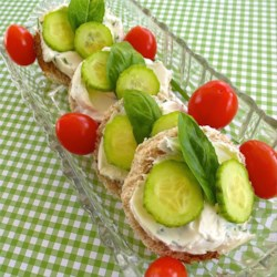 Christa's Cucumber Basil Tea Sandwiches Recipe - Delicate and savory little rounds of rye bread hold a creamy layer of cream cheese and chives, a couple of slices of cucumber, and a fresh basil leaf for the lightest, easiest tea sandwiches.