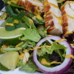 Tandoori Chicken Salad Recipe - Tangy grilled chicken atop a bed of greens mixed with onions, raisins, almonds, pineapple, mint sprigs, and lime.  Includes a zesty Indian-style salad dressing.