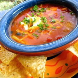 Quick Spicy Tomato Soup Recipe - Cream of tomato soup is added to sauteed red peppers and onion in chicken broth with olives, chilies and stewed tomatoes.  Serve over crushed tortilla chips with a dollop of sour cream and grated cheddar.