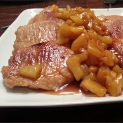 Caramel Apple Pork Chops Recipe - Succulent pork loin chops are paired brilliantly with slices of tart apple cooked in a satin-smooth sauce of butter, brown sugar, cinnamon and nutmeg. A few chopped pecans over the top make this a delectable autumn entree.