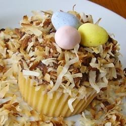 Easter Nests Recipe - Chocolate cupcakes topped with prepared frosting are covered with toasted coconut and a few colorful egg-shaped candies to make cute Easter birds'-nest cupcakes.
