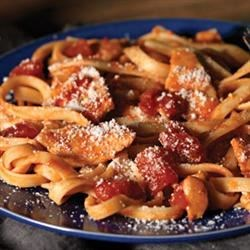 Chicken-Parmesan Pasta Toss Recipe - Chicken strips simmered in a chunky tomato sauce with cheese are tossed with hot cooked fettuccine--this dinner's on the table in 25 minutes!