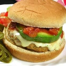 Ground Chicken Taco Burgers Recipe - Ground chicken blended with minced onion, garlic, and taco seasoning is a terrific alternative to regular hamburger patties. Topped with pepper jack cheese slices, avocado, jalapenos, and salsa on wheat buns, every bite sizzles with South-of-the-Border flavor.