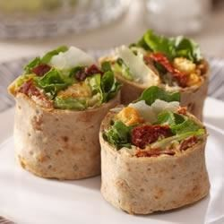 Caesar Salad Pinwheels Recipe - Sun-dried tomatoes in a cream cheese spread add color and creaminess to these delicious Caesar salad pinwheels.