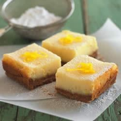 Creamy Lemon Squares Recipe - A creamy, lemon layer on a wafer cookie crust is dusted with powdered sugar and lemon zest just before serving in these light lemon bars.