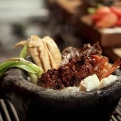 Rudy's Molcajete Mixto Recipe - This mixed grill of carne asada, nopales, chicken, shrimp, jalapenos, and chorizo sausage is served in a heated molcajete with queso fresco, salsa, avocado and lime for a delicious Mexican feast.