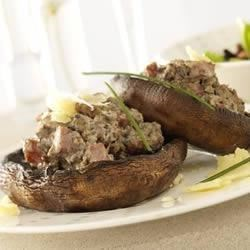 Stuffed Portobello Mushrooms Recipe - Stuffed with pork sausage, shredded and ricotta cheeses, onions and sun-dried tomatoes, these tasty mushroom caps are a sure crowd pleaser.