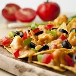 Swanson(R) Chicken Nachos Recipe - A cheesy chicken topping for this bed of nachos is spiked with the bold flavors of Pace(R).