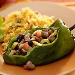 Chile Rellenos with Salsa Verde Cream Sauce Recipe - Poblano chile peppers are stuffed with a mixture of beef, onion, garlic, olives, raisins, and almonds for a tasty variation on a classic dish.