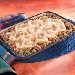 Garlic Mashed Potatoes and Beef Bake Recipe - This version of classic Shepherd's Pie features ground beef and vegetables in a savory sauce topped with mashed potatoes and baked until piping hot.