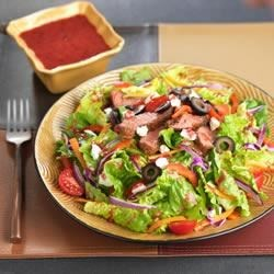 Blackened Steak Salad with Berry Vinaigrette Recipe - Seasoned, grilled flat iron steak is thinly sliced and served atop a romaine salad studded with roasted red peppers and feta cheese.